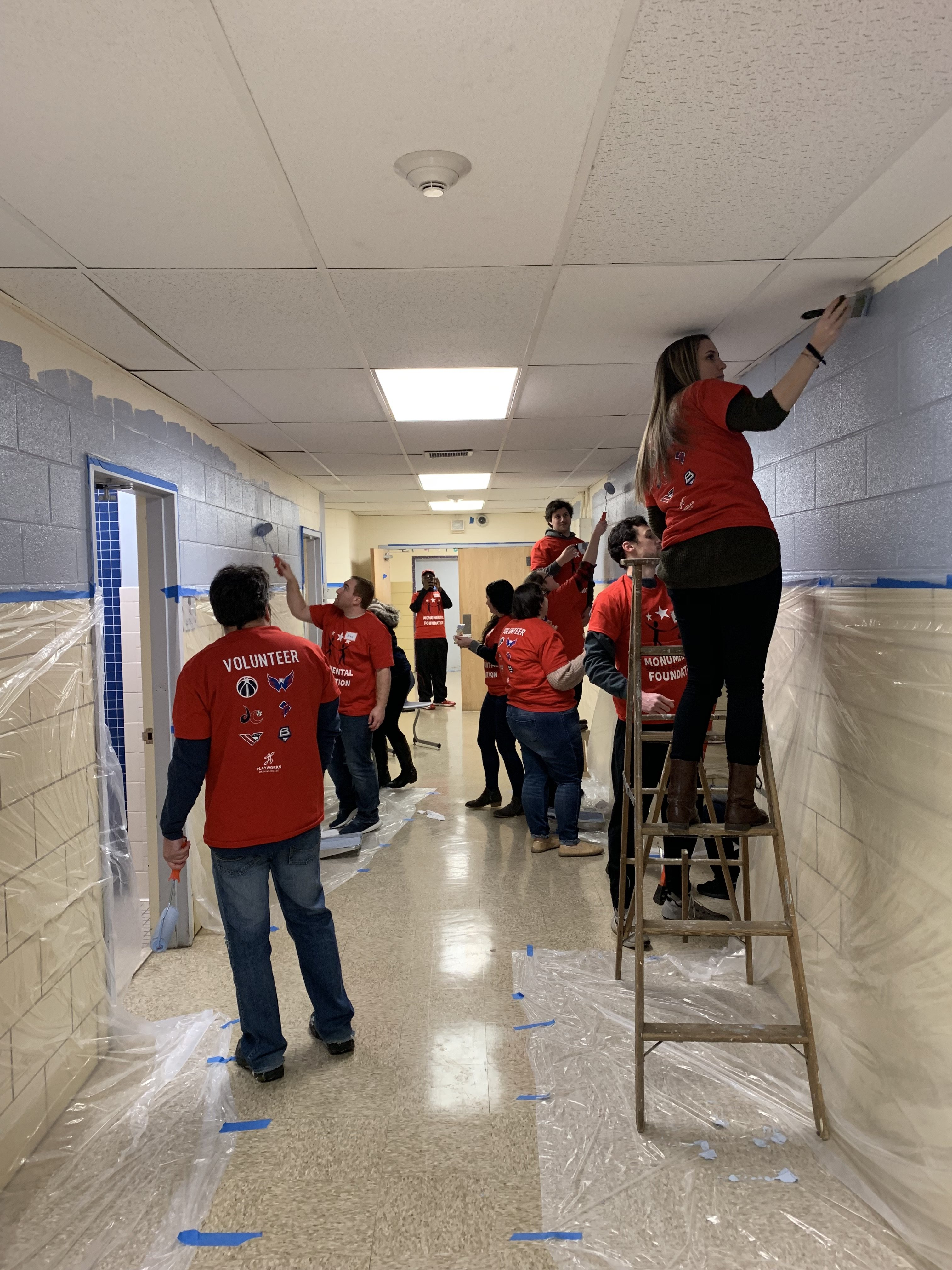 Several volunteers painting the hallways of Neval Thomas Elementary
