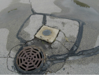 sewer cap and uneven cement